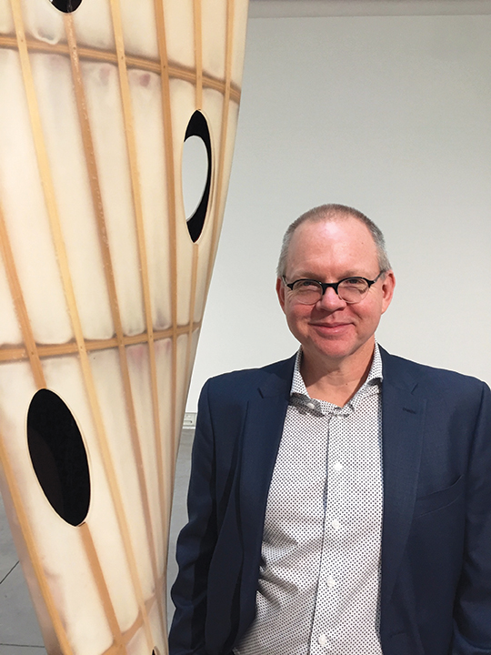 Tyler Stallings, the new director of the Frank M. Doyle Arts Pavilion at Orange Coast College, posing in front of a sculpture by Eric Johnson, in which he expresses his fascination with the DNA helix.