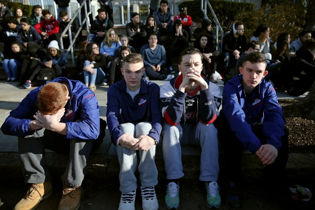 In this Feb. 28, 2018 photo, Somerville High School students sit on the sidewalk on Highland Avenue during a student walkout at the school in Somerville, Mass. A large-scale, coordinated demonstration is planned for Wednesday, March 14, when organizers have called for a 17-minute school walkout nationwide to protest gun violence. (Craig F. Walker/The Boston Globe via AP)
