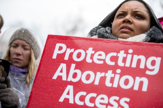"A pro-abortion rights supporter holds a sign that reads ""Protecting Abortion Access"" during a rally outside the Supreme Court in Washington, Tuesday, March 20, 2018, as the Supreme Court hears arguments in a free speech fight over California's attempt to regulate anti-abortion crisis pregnancy centers. (AP Photo/Andrew Harnik)"