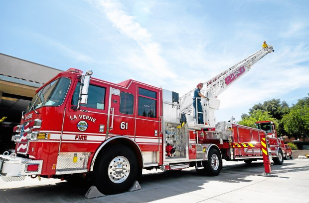 La Verne Fire Captain Dave Benson and firefighter Victor Amezcua, stand atop the departments brand new 100-FOOT aerial ladder fire truck at the La Verne Fire Station in downtown La Verne, Friday, July, 31, 2015. The new fire truck, paid for with  fees levied on developers for new projects, was built by Pierce Manufacturing in Appleton, Wisconsin. (Photo by John Valenzuela/Inland Valley Daily Bulletin)