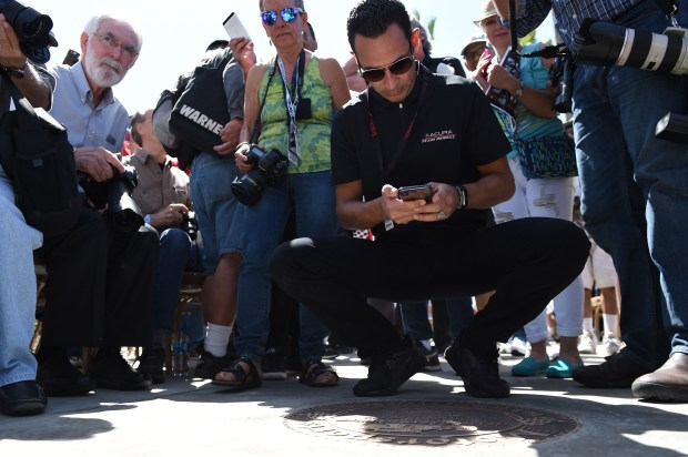 Helio Castroneves takes a picture of his plaque on the Long Beach Motorsports Walk of Fame, a City of Long Beach and Grand Prix Association of Long Beach joint project. Castroneves, from Sao Paulo, Brazil, won in an Indy car at Long Beach in 2001, and captured the 1997 Indy Lights race at Long Beach as well. Being honored on the walk does not indicate the driver is retired by any means, in fact both drivers will be racing this weekend. Long Beach April 12, 2018. Photo by Brittany Murray, Press Telegram/SCNG