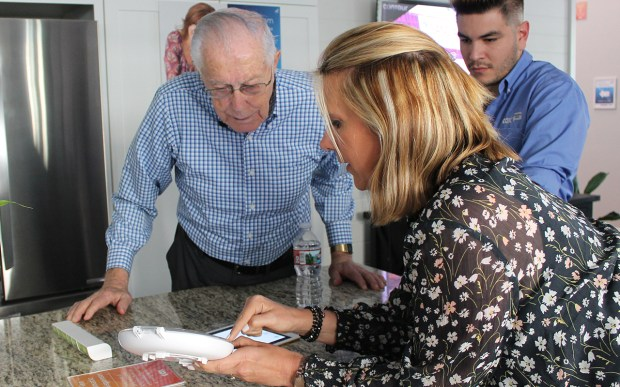 Jennifer Cobb, right, shows Mission Viejo resident Ken Ray a smart pill dispenser that helps seniors stay on schedule with their medications. The product was demonstrated at the Cox Communications Senior Smart Home event on April 19, 2018.(Courtesy of Gina Ray)