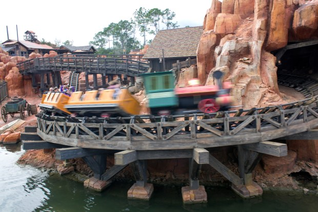 "A train speeds around the bend on the Big Thunder Mountain Railroad, an attraction that can seem much less ""open"" when only one train is running. (File photo by Mark Eades, Orange County Register/SCNG)"