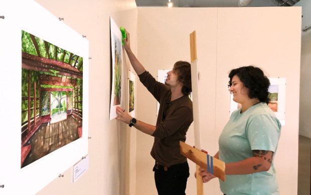 Students Ed Milanino and Briana Aldave hang paintings in the the Orange County Agricultural and Nikkei Heritage Museum at the Fullerton Arboretum. Learning how to mount an exhibition is part of what they learned in class. (Photo courtesy of Lawrence Yun)