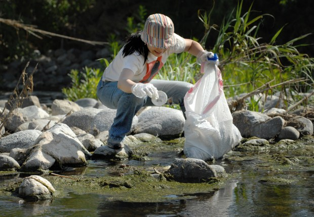 "Mikiko MacAdams pulls a bit of trash out of the LA River. Marsh Street Park, near Riverside Dr. and the 5 freeway was one of several locations where volunteers gathered to pick up trash in the Los Angeles River. Friends of the Los Angeles River hosted ""La Gran Pimpieza,"" also known as the 21st annual Great L.A. River Cleanup, at 14 different areas from the San Fernando Valley and into Los Angeles. For more information check out www.folar.org or call 323-223-0585 to talk to friends of the Los Angeles River. Los Angeles, California, 5/08/2010. photo by John McCoy/staff photographer"