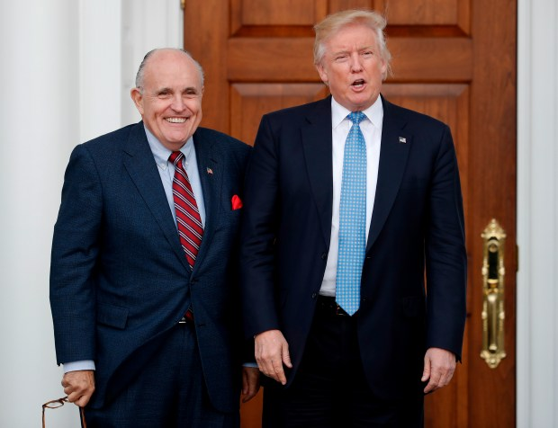 In this Nov. 20, 2016 photo, then-President-elect Donald Trump, right, and former New York Mayor Rudy Giuliani pose for photographs as Giuliani arrives at the Trump National Golf Club in Bedminster, N.J. Giuliani is joining the legal team defending President Trump in the special counsel's Russia investigation. (AP Photo/Carolyn Kaster, File)