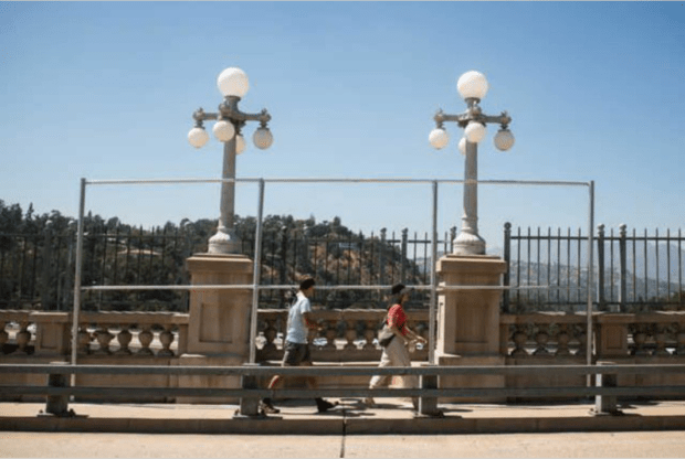 Walkers pass a Colorado Street Bridge alcove on Thursday, July 20, 2017 where poles have been placed to support wire mesh fencing. The City of Pasadena says the alcoves and their benches are being used by suicide jumpers to more easily get over the bridge's fencing. (Photo by Sarah Reingewirtz, Pasadena Star-News/SCNG)