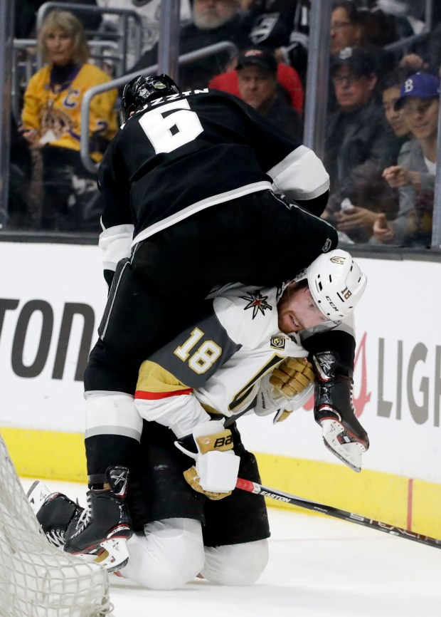 Los Angeles Kings defenseman Jake Muzzin, top, gets tangled up with Vegas Golden Knights left wing James Neal during the first period of Game 3 of an NHL hockey first-round playoff series in Los Angeles, Sunday, April 15, 2018. (AP Photo/Chris Carlson)