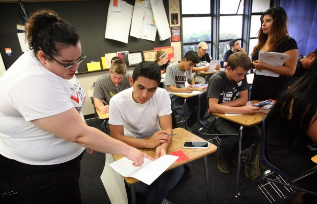 Lisbeth Aguilar of Mi Familia Vota, left, helps 16 year old senior Leonardo Sepulveda with his voter registration form on Friday, Oct. 16, 2015. Mi Familia Vota is held a voter registration presentation at Canyon Springs High School to entice students to register to vote. Inland community organizers described the governor's signing of AB 1461 as a watershed moment in their quest of increasing Latino political participation.