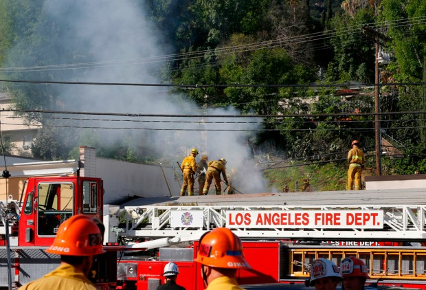 Los Angeles firefighters knock down hot spots on the roof of a recording studio in Studio City on Saturday, April 14, 2018. Officials say two people were killed and at least three others were hurt when flames ripped through the studio. Fire spokeswoman Amy Bastman says crews found heavy smoke when they responded shortly before 7 a.m. Saturday to the business on Cahuenga Boulevard. (AP Photo/Damian Dovarganes)