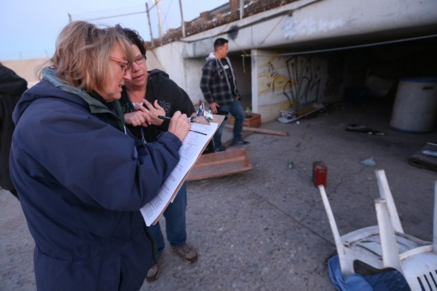 Luisa Tassan, a volunteer from Riverside, left, and Jill Kowalski, with the Riverside County Department of Public Social Services' Homeless Program Unit, fill out a survey after interviewing homeless people living in a flood control channel in Jurupa Valley on Tuesday, Jan. 23, 2018. (File photo by Stan Lim, The Press-Enterprise/SCNG)