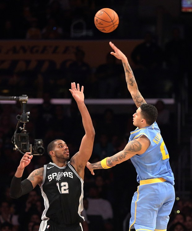 Lakers forward Kyle Kuzma shoots as Spurs forward LaMarcus Aldridge defends during the final seconds of overtime in their game last week at Staples Center. (AP Photo/Reed Saxon)