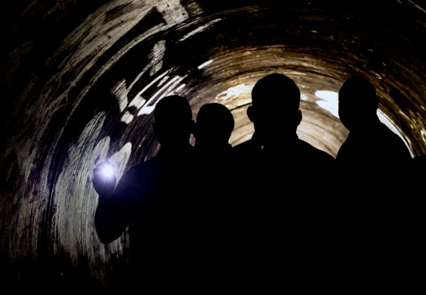 Santa Ana police officers shine their flashlights in a musty concrete culvert that goes under Main Street in Santa Ana and is used by homeless people. (Photo by Mindy Schauer, Orange County Register/SCNG)