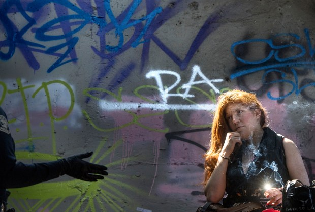 Chelsea Cade, 27, chats with Santa Ana police homeless liaison officer Cassandra Hawkins beneath the Broadway overpass where a group of homeless people have been living. (Photo by Mindy Schauer, Orange County Register/SCNG)