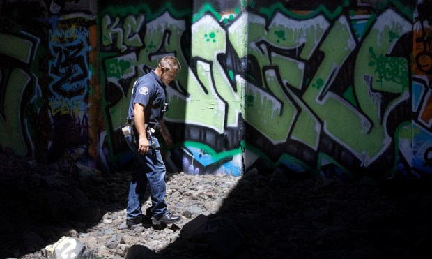 Santa Ana Police make their rounds to an area beneath the Broadway overpass that has been populated by as many as 70 homeless people. (Photo by Mindy Schauer, Orange County Register/SCNG)