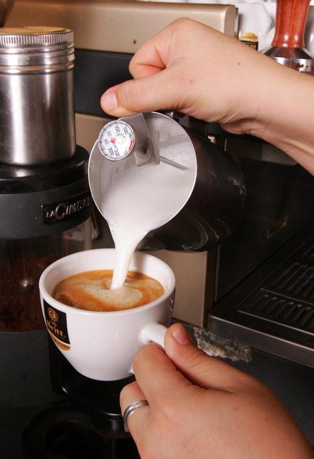 """Una camarera sirve una taza de café con leche en una cafetería costarricense. Costa Rica dispone de inmejorables condiciones agronómicas para producir café de la variedad Arábiga, por lo que el país se ha concentrado en mejorar cada vez más los estándares de calidad de su """"grano de oro"""". (EFE/Jeffry Arguedas/rsa)"""