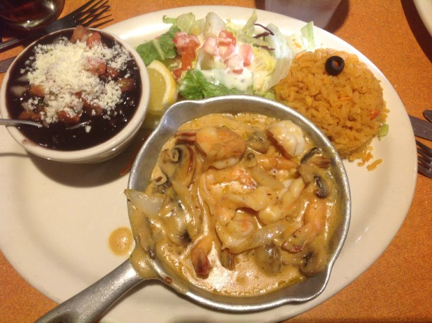 La Concha Coastal Mexican Grill's shrimp in a creamy chipotle sauce contains sliced mushrooms and onions and is accompanied by black beans, house rice and a small salad. (Photo by Dorene Cohen)