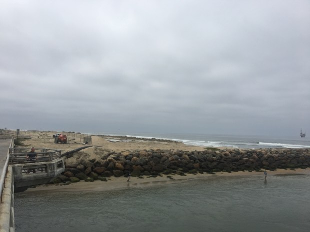 The ocean inlet to the Bolsa Chica wetland is once again being dredged, with the sand being pumped onto the beach immediately to the south, as seen in this May 10, 2018, photo. Staff photo by Martin Wisckol.