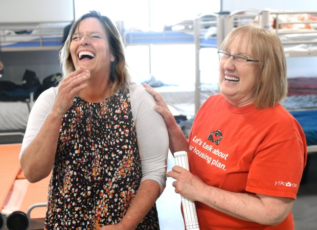 Bridget Powers shares a laugh with her friend Cathie Allman, a call center specialist at Bridges. (Photo by Bill Alkofer, Contributing Photographer)