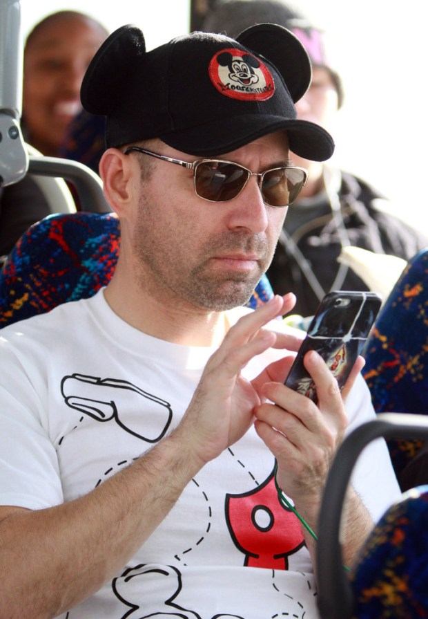 Passenger Mario Tovar, of Riverside, checks his phone as he rides a Riverside Transit Agency bus to Disneyland as the service debuts on Jan. 14, 2018. On Sunday, May 13, RTA added a late bus to the popular service. (File photo by Micah Escamilla, Contributing Photographer)