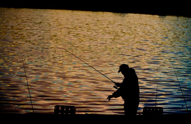 As the colors of the rising sun reflect off the surface of Santa Ana River Lakes, a fisherman untangles his line.(PHOTO BY, BRUCE CHAMBERS, ORANGE COUNTY REGISTER/SCNG)
