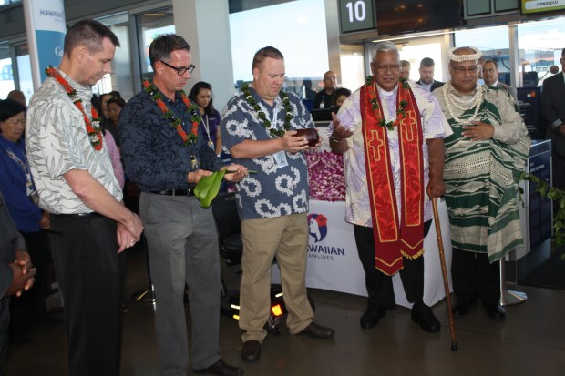 A religious leader flown from Hawaii specifically for the occasion blesses the gate at Long Beach Airport Friday, June 1, before the first Hawaiian Airlines flight.