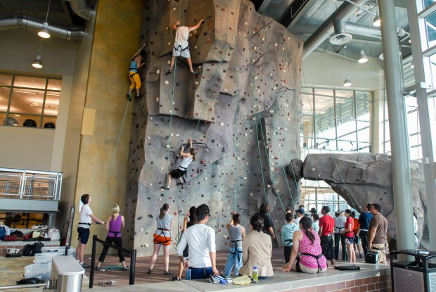 Students climb an indoor rock wall that overlooks the entrance to the Student Recreation Center. The 95,000-square-foot facility is funded by student fees. (Photo courtesy of Cal State Fullerton)