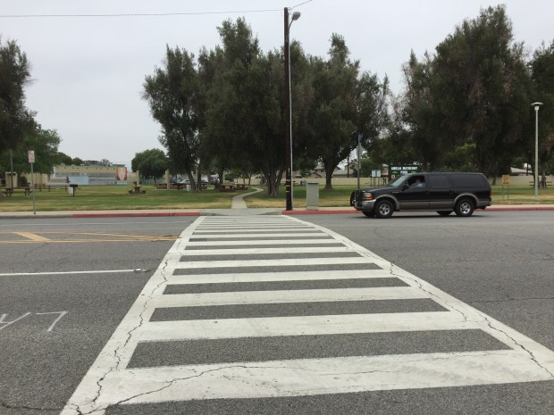 A motorist drives across a crosswalk over Meyer Road at Mayberry Park. Los Angeles County plans to add flashing overhead LED lighting to make the intersection safer. Staff photo by Mike Sprague