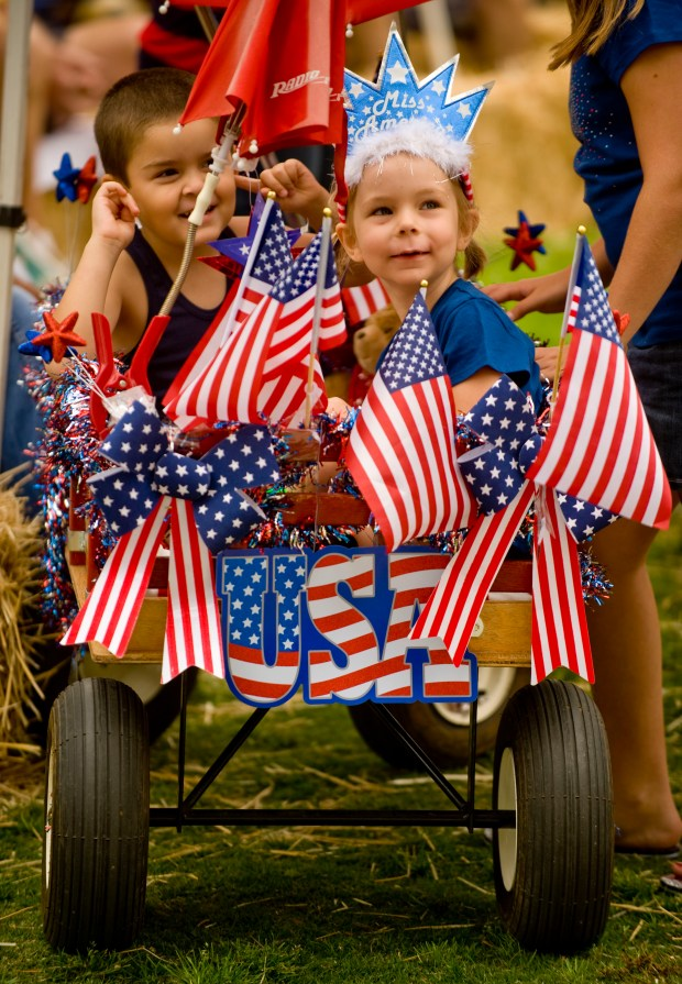 Savannah Schlottach, 9, right, sits with Cruz Mendoza, 4, in her ride that won first place for best decorated wagon in the Kiddie Parade Wednesday at the 33rd Annual Brea Country Fair held at City Hall Park. ///ADDITIONAL INFO: breacountryfair.0705 - 7/4/12 - Photo by PAUL RODRIGUEZ, THE ORANGE COUNTY REGISTER - Brea's old fashioned Country Fair was held at City Hall Park featuring live entertainment, a kiddie parade, beautiful baby contest, rides and food.