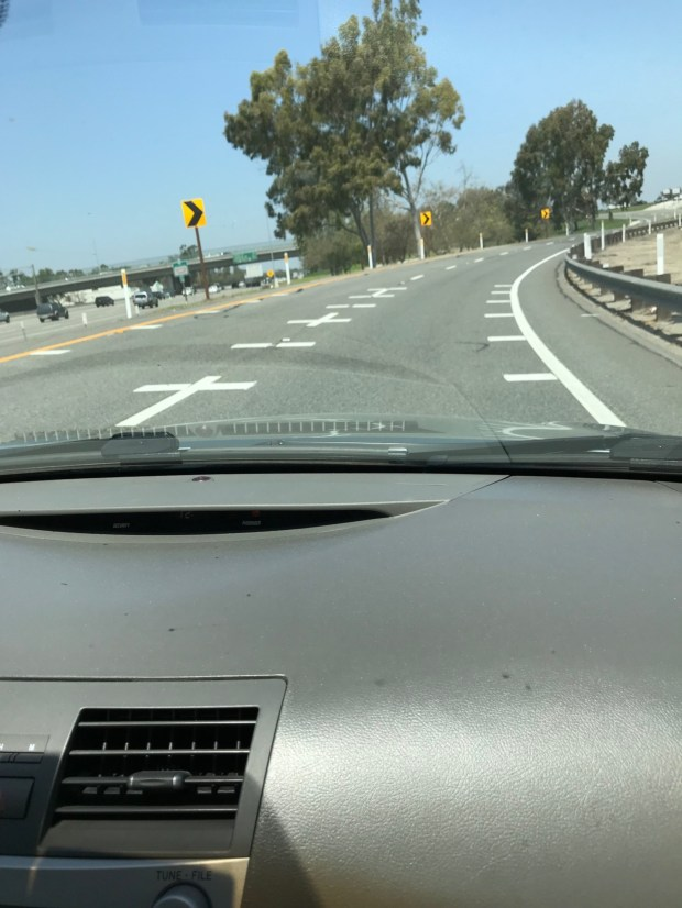 White lines that are painted perpendicular to the regular lines that divide lanes are meant to be a visual cue for drivers to slow down on a curve. (Couresty of Jerry Donaldson)