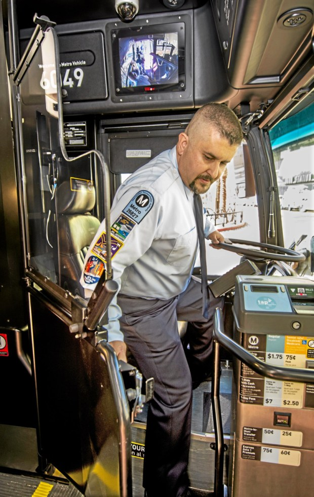 Metro bus operator Juan Navarro, demonstrating safety equipment as he closes door with metal bottom and Plexiglass top on a retrofitted bus at the LA County Metropolitan Transportation Authority on March 20, 2015. (Photo by Walt Mancini/Pasadena Star-News)