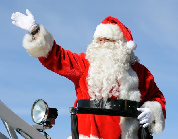 A waving Santa Claus rides on top of a Hemet Fire Dept. firetruck in the Hemet Christmas Parade Saturday. (File Photo)