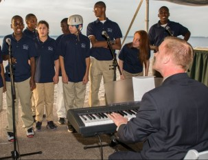A man plays a keyboard and directs a group of adolescents singing at the 2013 Howard F. Treiber Memorial Golf Outing