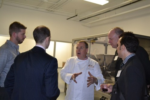 man in chef coat speaking to four other men