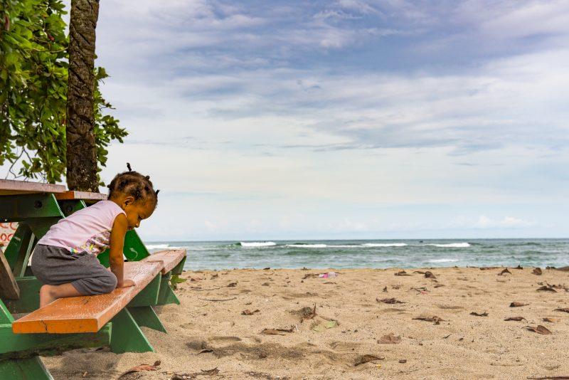 playa soledad Capurganà nel Chocò Colombia bambina in spiaggia sopra ad una panchina