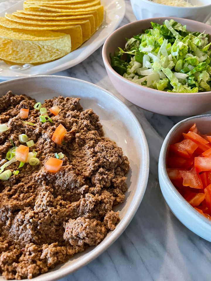 taco meat with taco shells, tomatoes, lettuce and cheese
