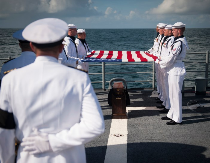 Members of the U.S. Navy Ceremonial Guard hold an American flag over the cremains of Apollo 11 astronaut Neil Armstrong during a burial at sea service aboard the guided-missile cruiser Philippine Sea. (Credit: Bill Ingalls, NASA)