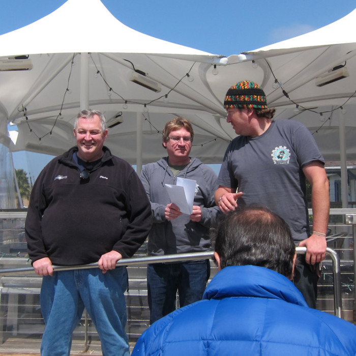 "Philip McCaleb (left) with Alex Cohn and Steve Bailey of Motorsport Scooters at the Genuine ""Family Reunion"" event in San Diego, March 2013.  Top photo: Philip McCaleb (front, center, with water bottle) with Genuine owners at a customer appreciation ride in Los Angeles, March 2012."