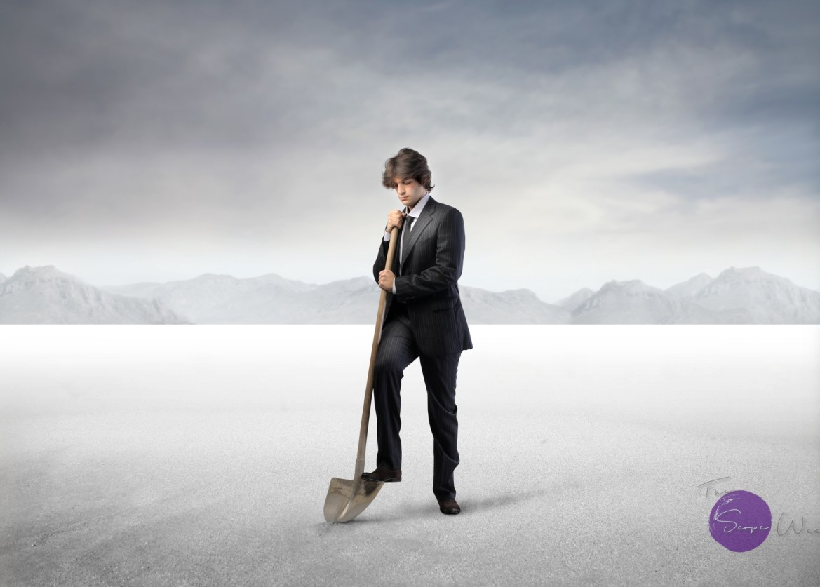 Startup | Businessman digging with a shovel in a desert