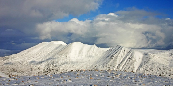 Photo of Foinaven wreathed in January snow, from the summit of Arkle
