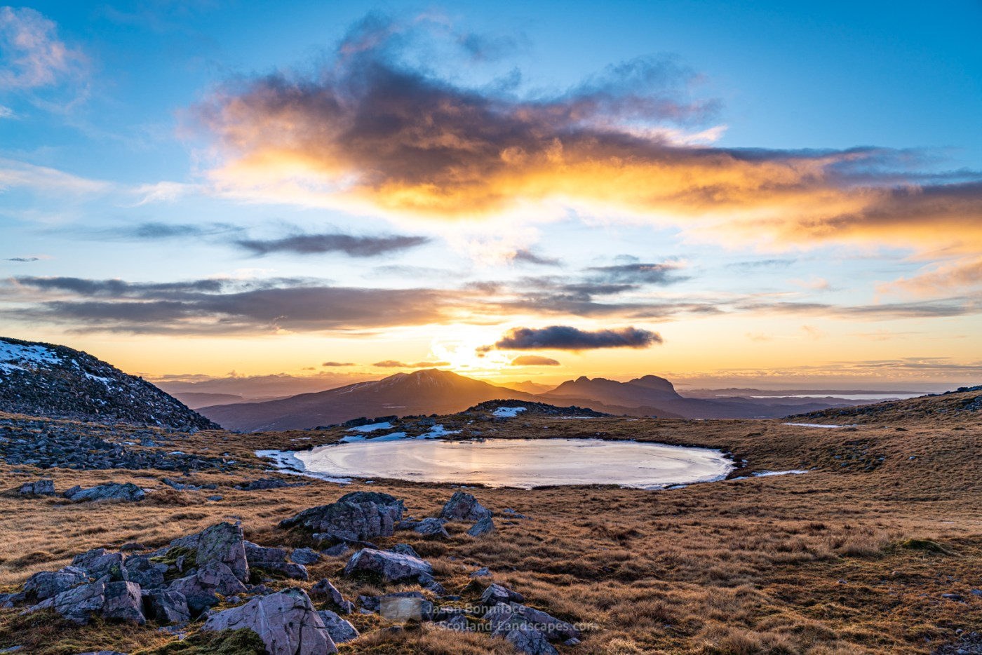 An afternoon glow as the sun descends behind Canisp, Stac Pollaidh and Suilven