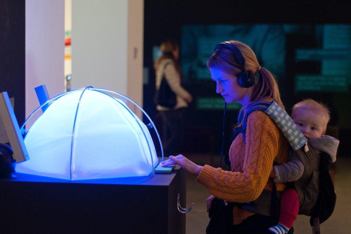 A woman presses a button on a plinth, in front of a small translucent dome which is glowing blue. There is a baby in a backpack on her back, who is looking at the camera.