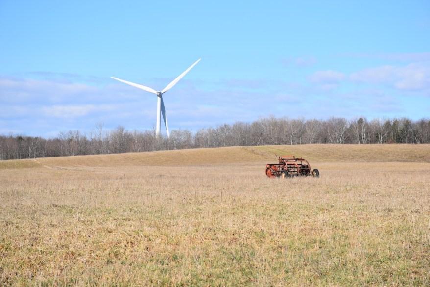 A wind turbine spins behind a field along Turnpike Rd - FLT M11