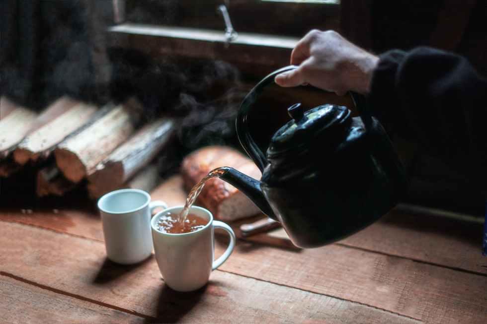 person pouring tea in white ceramic mug