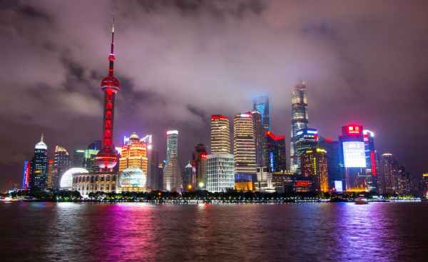lighted buildings during nighttime near body of water. China