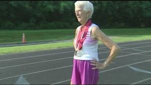elderly lady wearing a race walking medal around her neck.