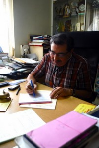 Image of Dr. Pendsey sitting at his desk at his clinic