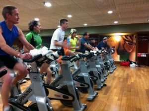 Picture of everyone lined up on spinning style stationary bikes at Lifetime Fitness