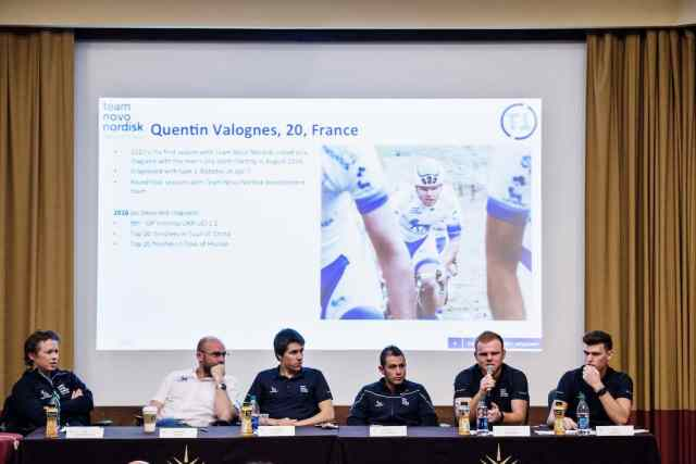 Panel of Team Novo Nordisk cyclists with Quentin speaking into a microphone