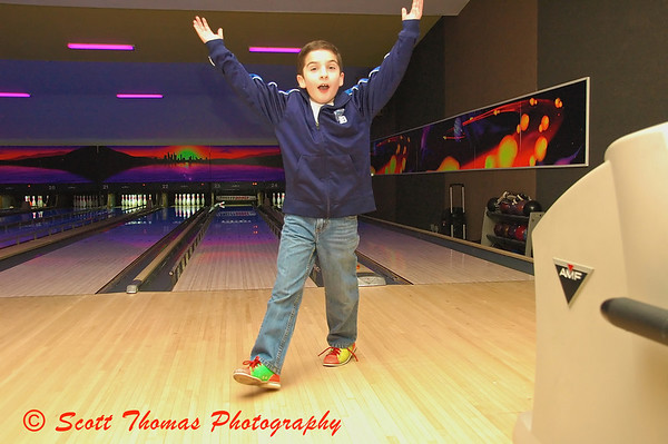 During his party, my nephew raises his hands in celebration after picking up a spare.